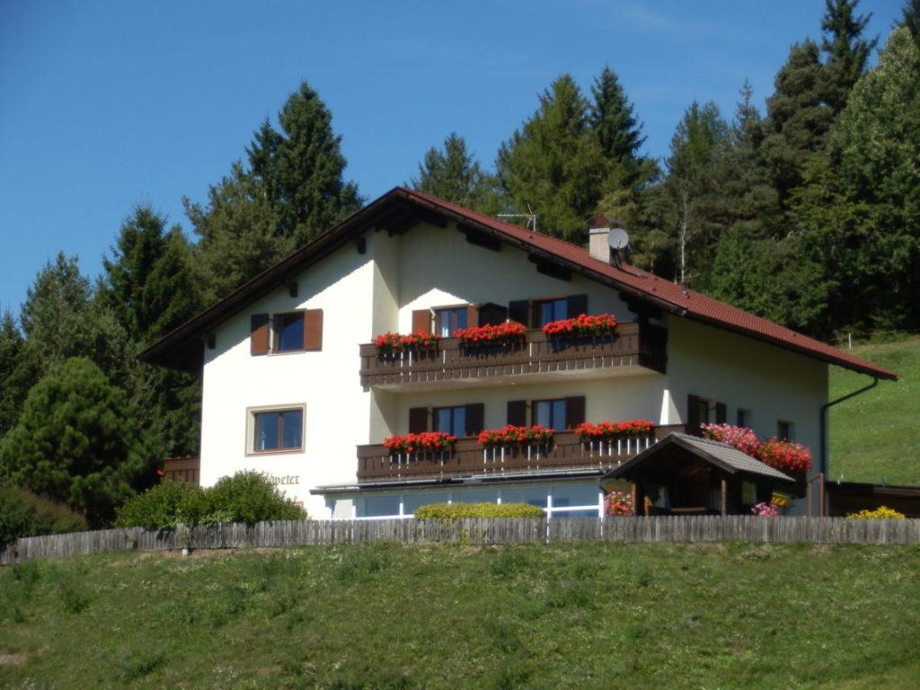 Casa con due balconi circondata da prati e boschi