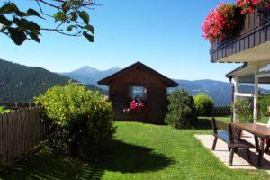 Gartenhütte im Grün mit Bergblick unter strahlend blauem Himmel